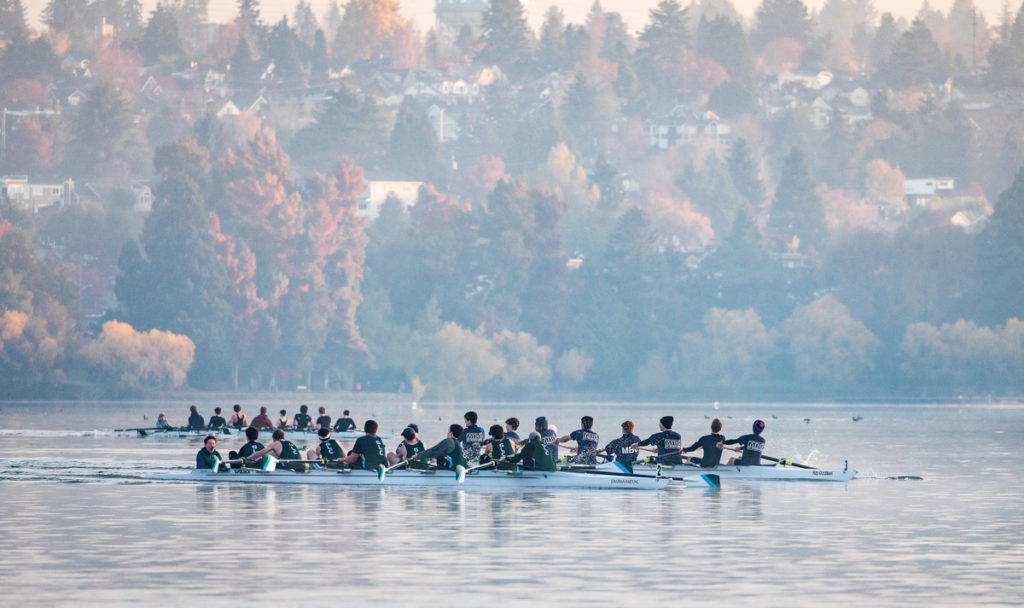 Three eight-person rowing shells on Green Lake at the 2019 Frostbite Regatta.